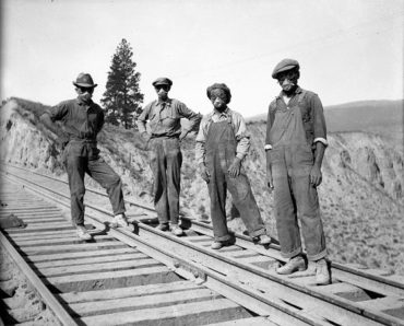 Four men in dust marks standing on a railway
